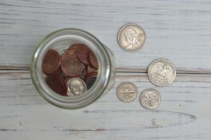 Picture showing various US coins on a table and in a jar.