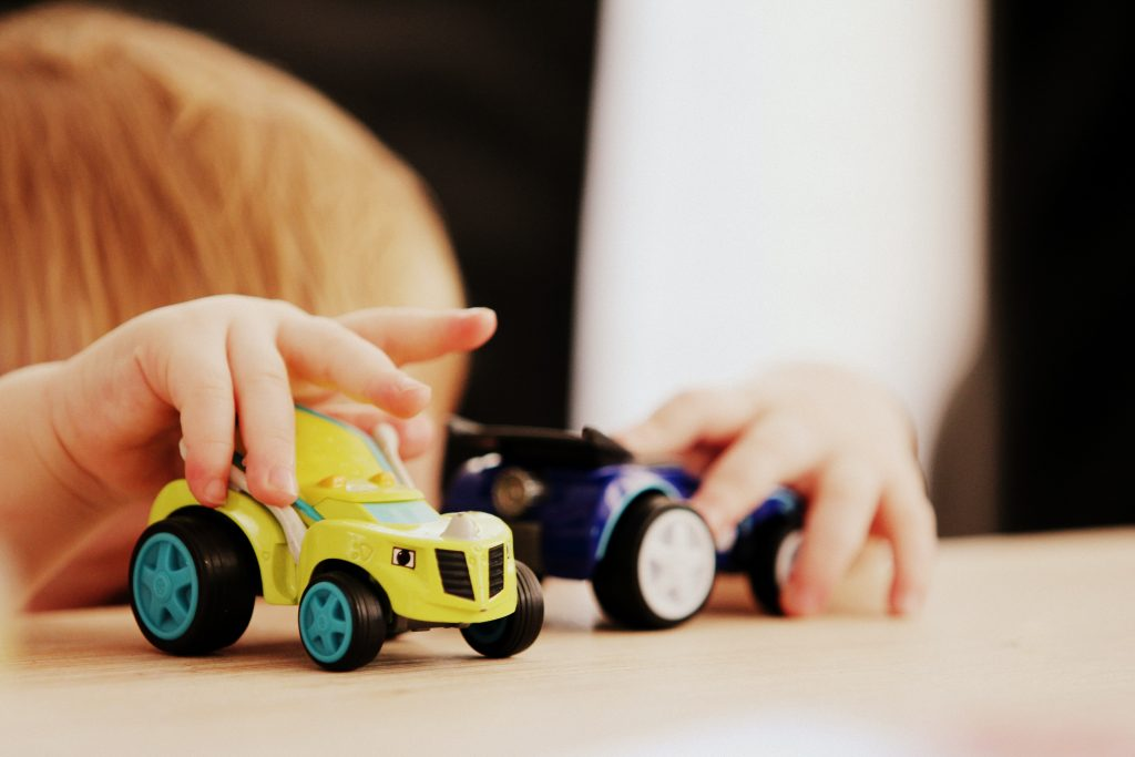 Picture of a kid playing with two toy cars.
